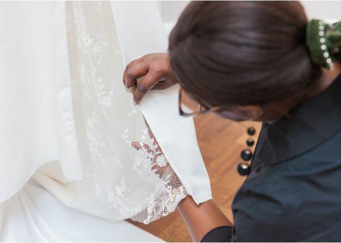 dressmaker pinning a dress on a mannequin