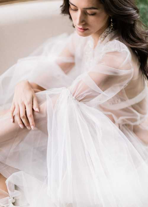 Fine art photo of a bride wearing a tulle wedding dress on the morning of the wedding