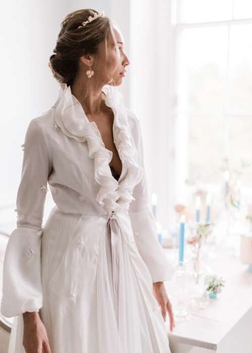 Elegant bride looking out of the window wearing a long sleeve bridal gown designed by Oui Madam Bridal , Bespoke Wedding Dresses London UK