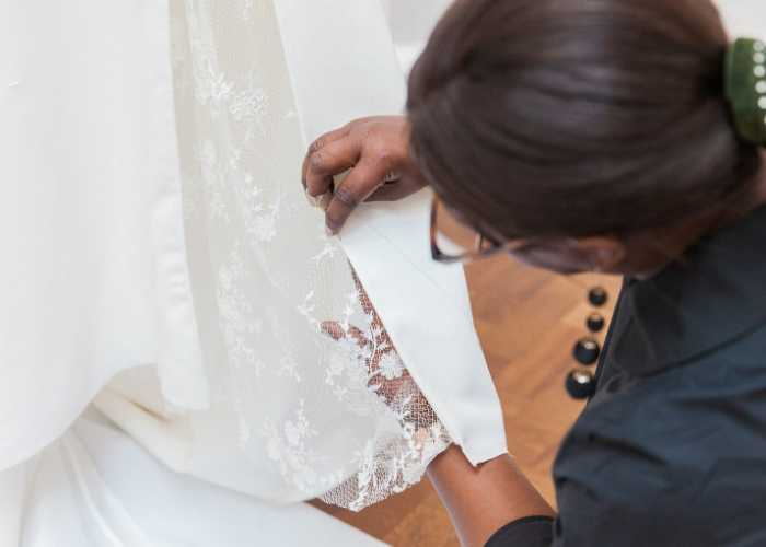 wedding dressmaker hand sewing a lace wedding dress