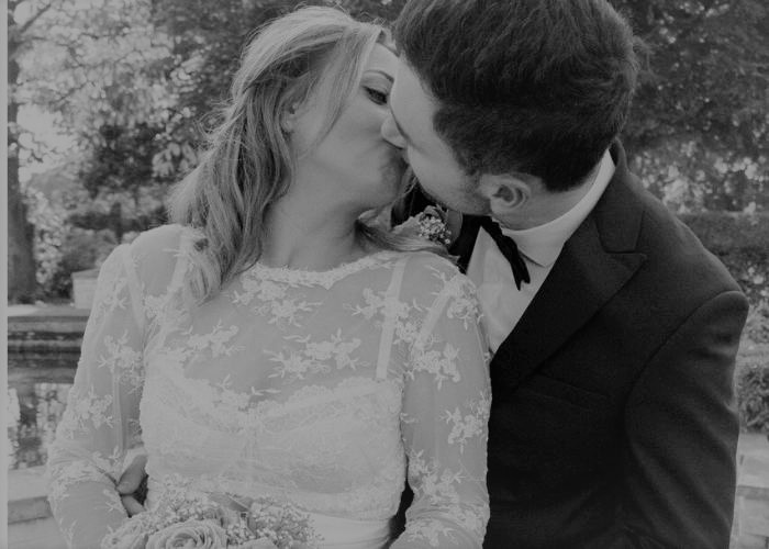 bride and groom kissing - bride wearing a lace bridal top