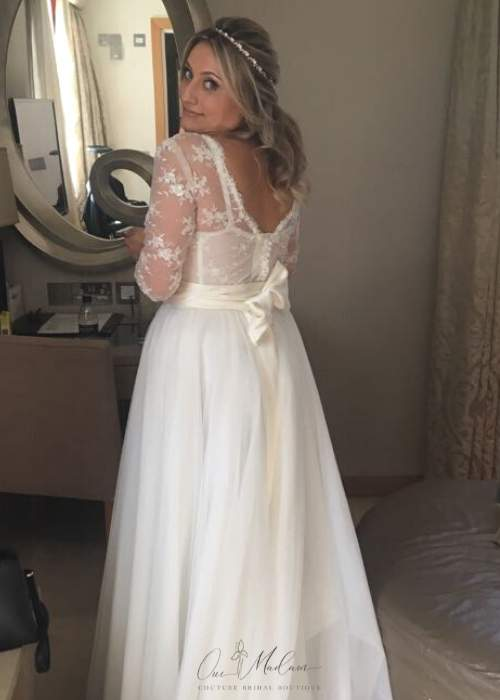 bride wearing lace bridal top and looking in mirror