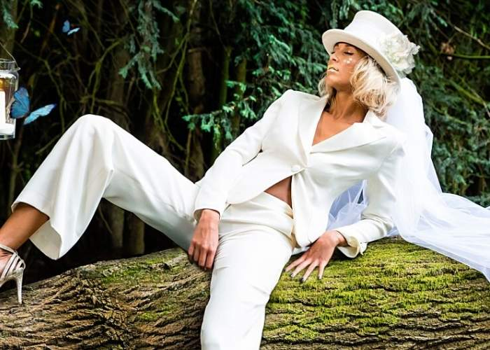 Bespoke Bridal Dress Makers London, unique wedding dresses, birde wearing a two piece bridal trouser suit sitting on a tree.