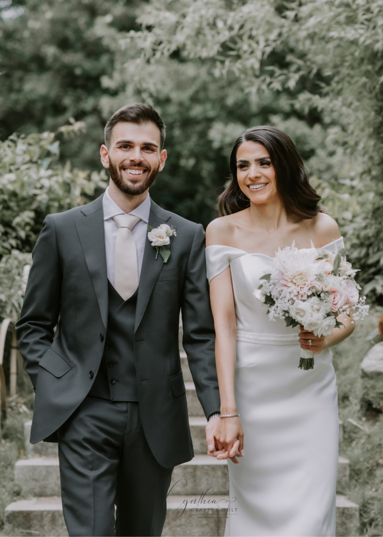 groom holds brides hand at fusion wedding